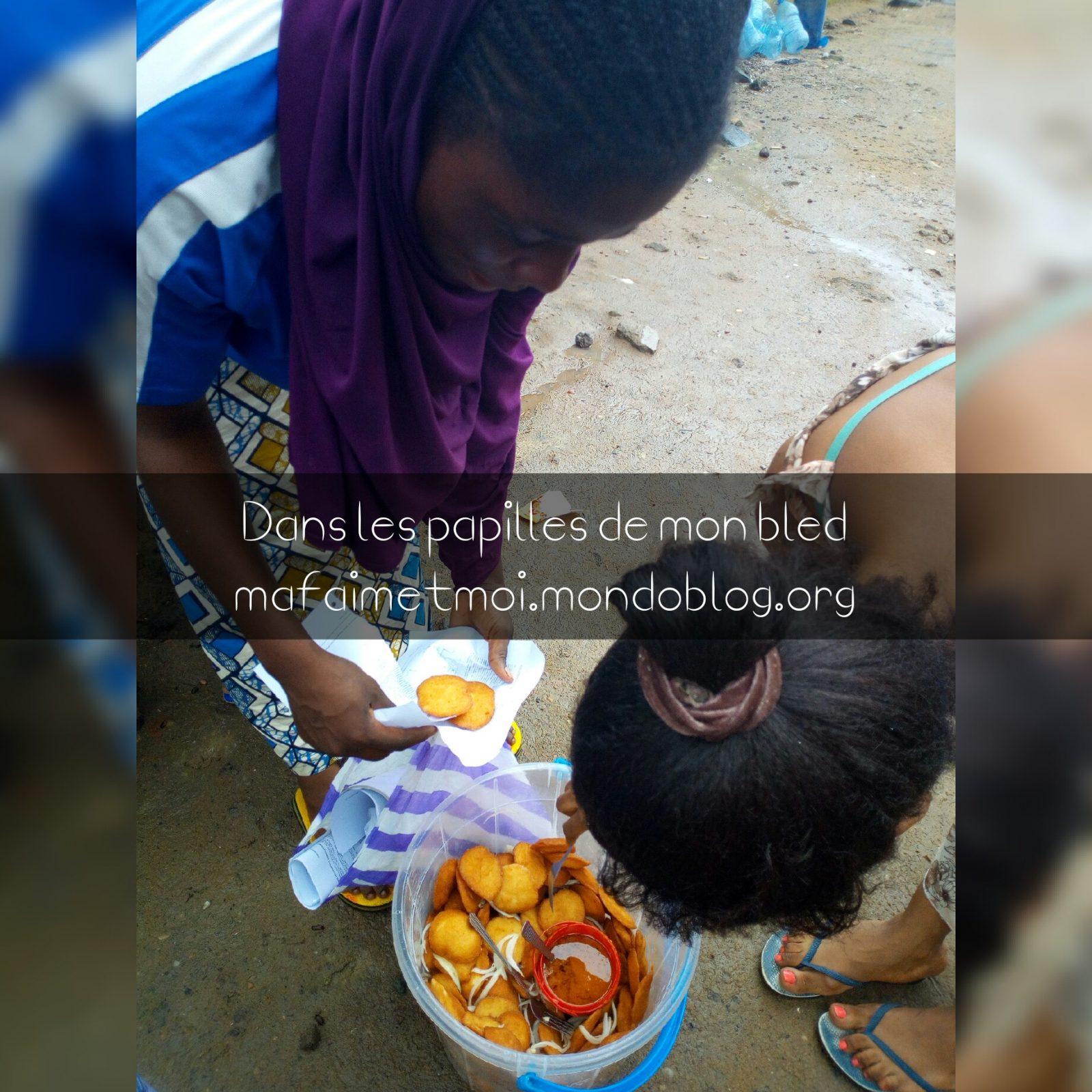 Vendeuse de beignets koki servant une cliente / Crédit Photo : Votre espionne culinaire